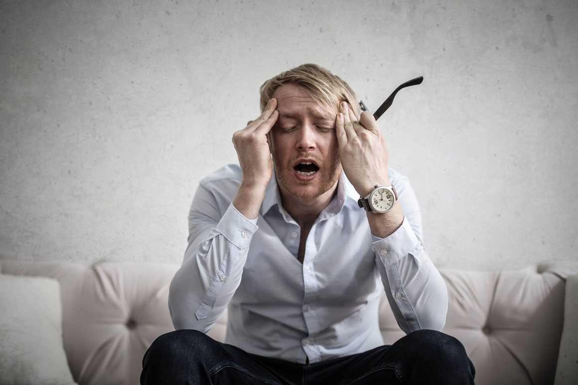 A man holding his head in frustration.