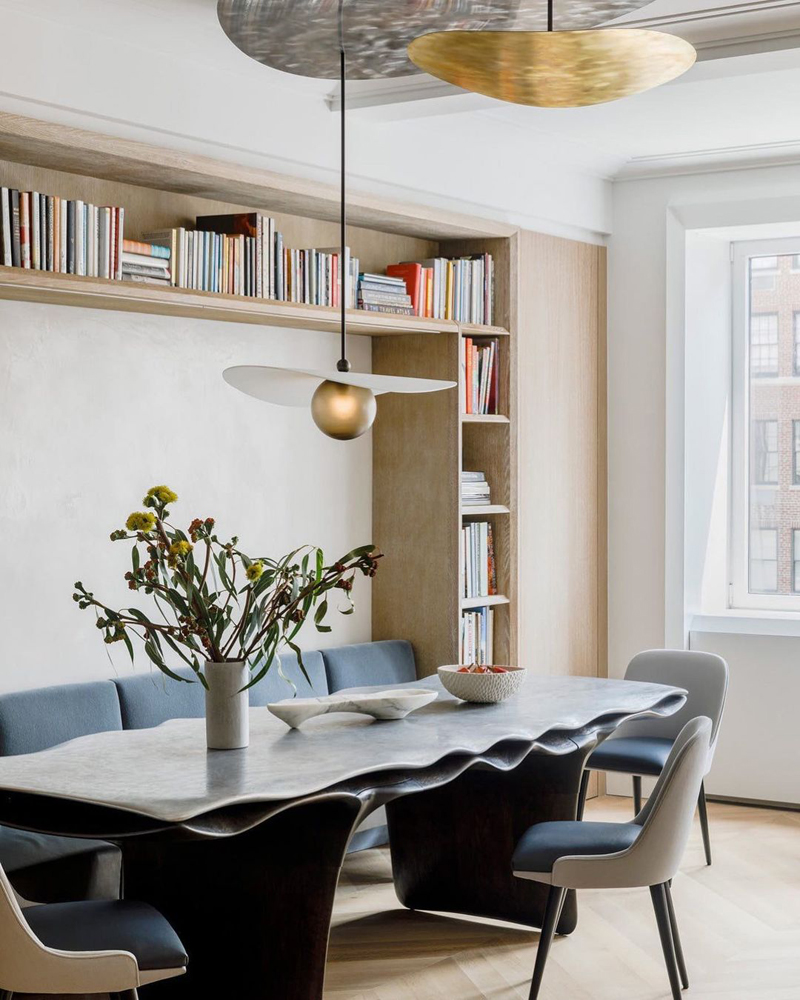 A chic interior of a dining area using contrasting geometric and natural forms.