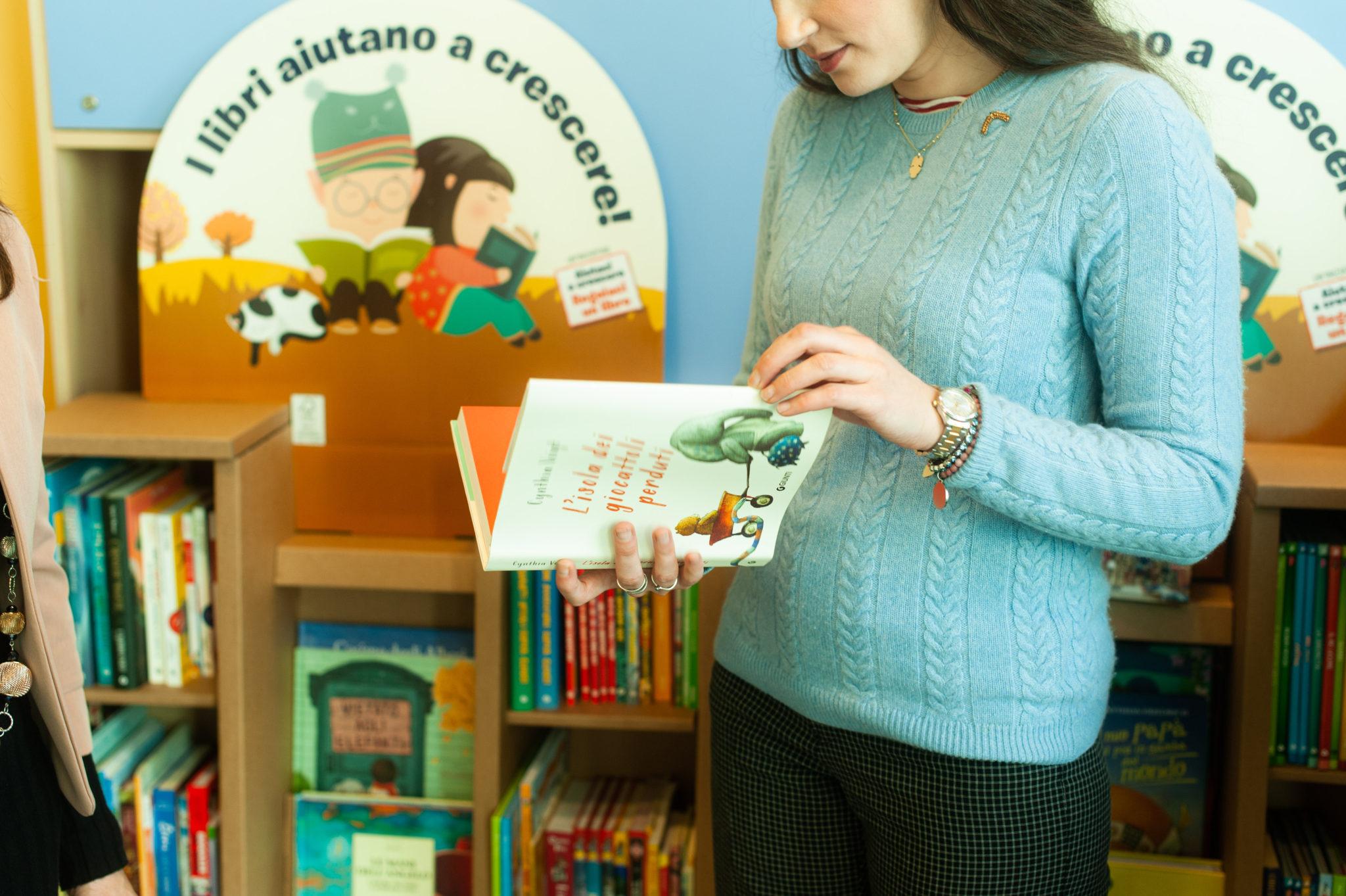 Una ragazza sfoglia uno dei libri donati