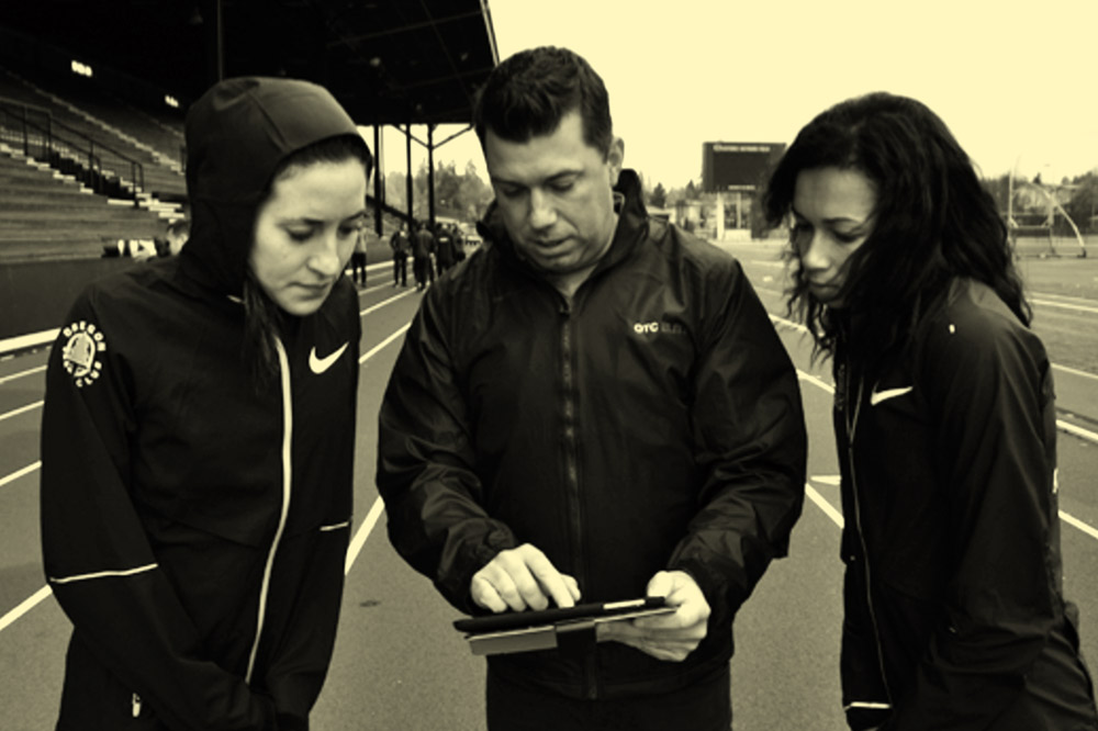 Orreco team showing software to athletes on an athletics track