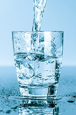 A glass of splashing ice water reminding you to enjoy fresh water on a regular basis.
