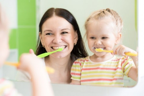 mother and child brushing their teeth together