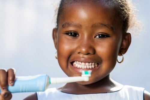 little girl holding up an electric toothbrush