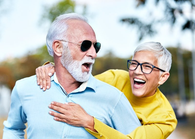 Older couple laughing at the beach