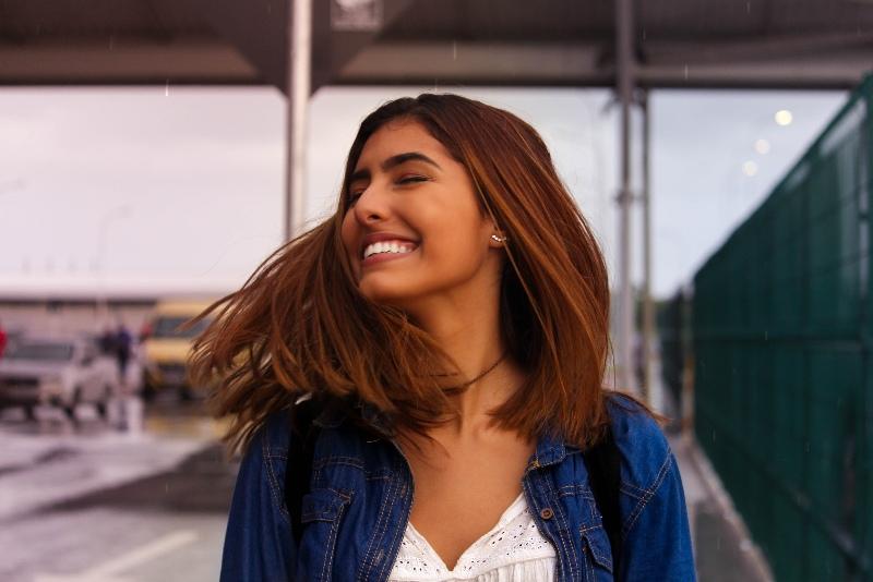 woman in denim jacket smiling