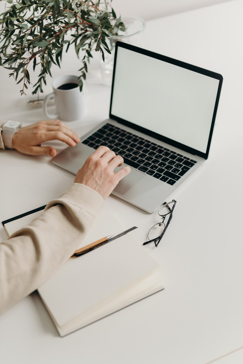 person using laptop computer on white desk