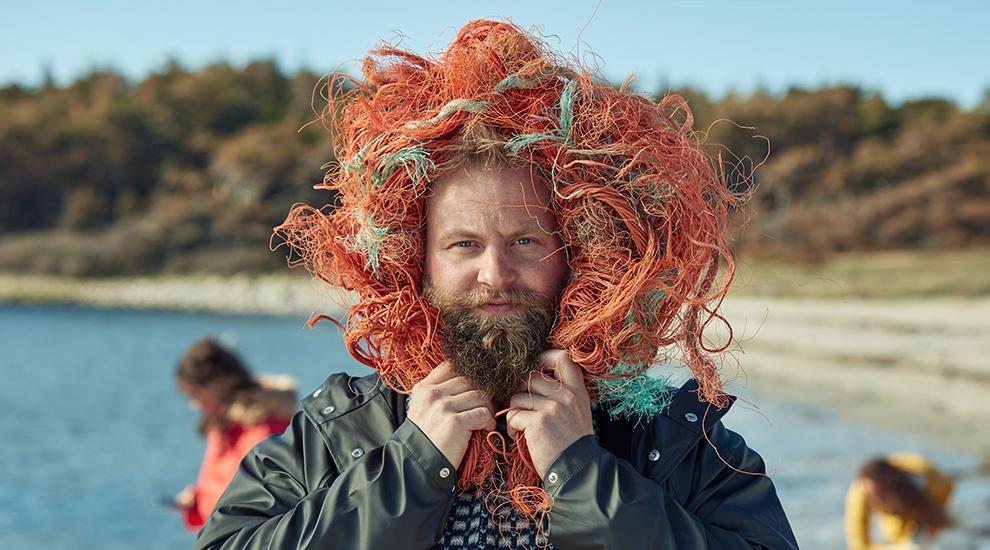 Mann med løvemanke laget av oransje tau funnet på strand