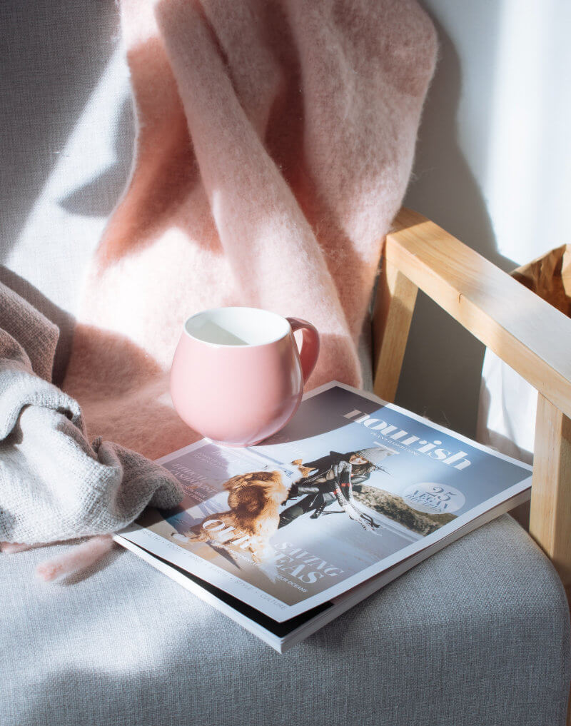 Cup of tea resting on a magazine on chair with pink throw