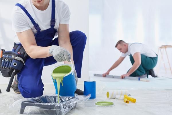 Maler bereiten ihren Arbeitsplatz vor, Farbe wird abgefüllt, Tapeten zugeschnitten