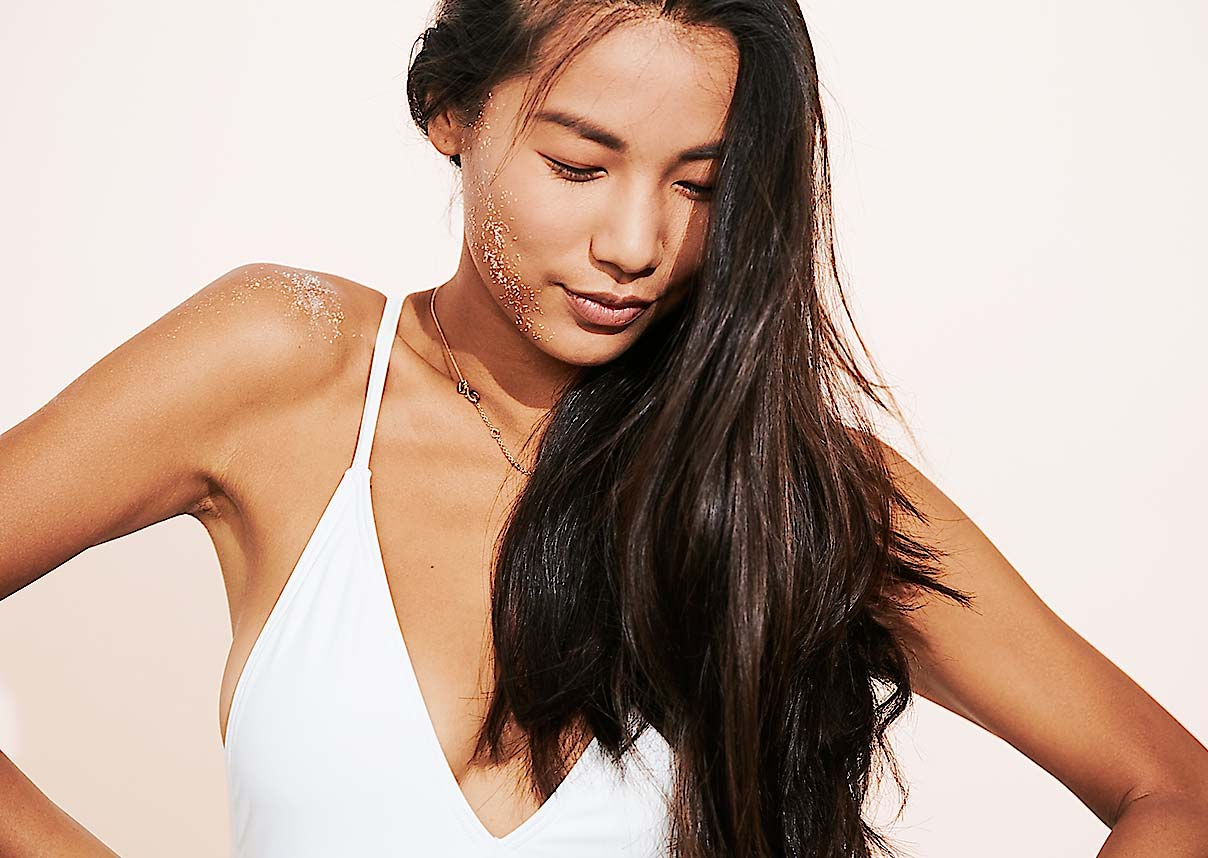 Asian woman in a white swimsuit with tanned skin