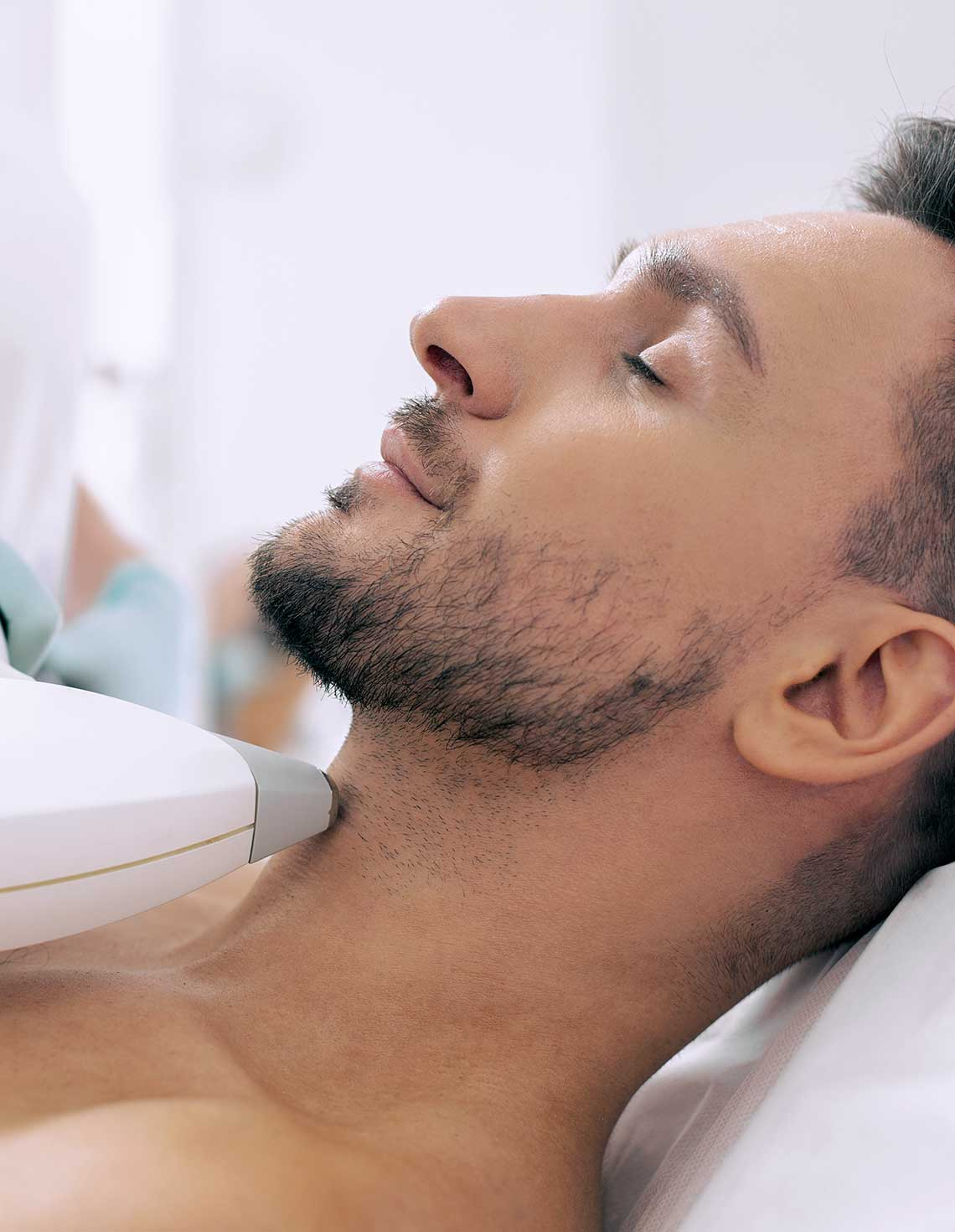 Man with a stylish beard having laser hair removal on his neck