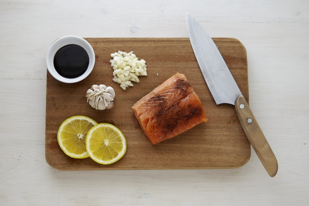gray knife and orange fish on wooden chopping board
