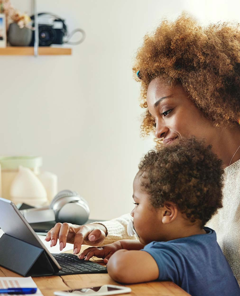 An african american woman working on a tablet with her small child next to her.