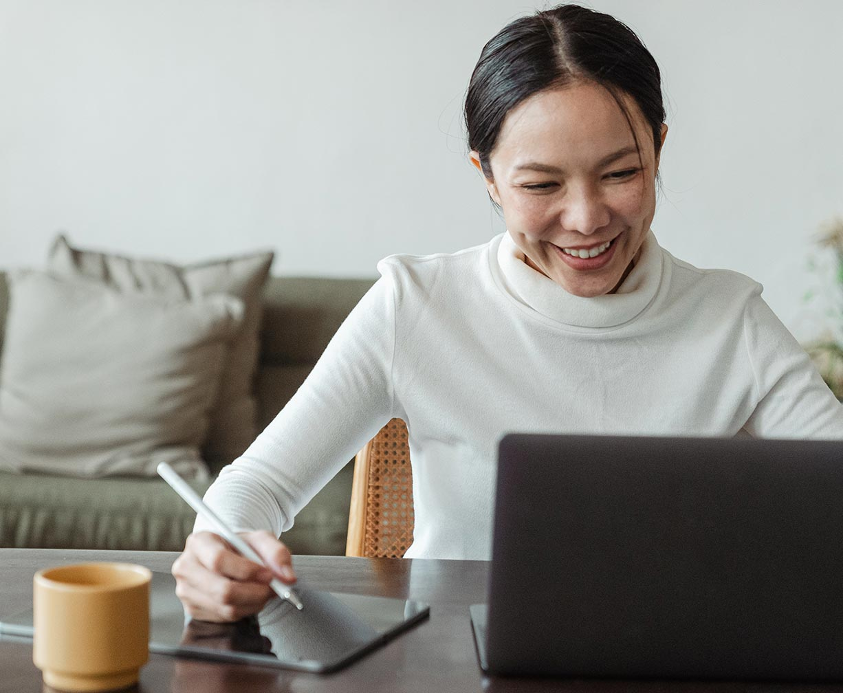 An asian woman smiling at her computer and drawing something on her tablet computer beside her.