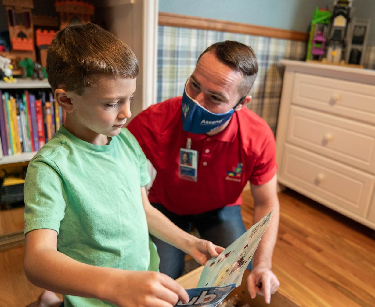 An ABA therapist wearing a red shirt and blue mask working with a small child in a green t-shirt.