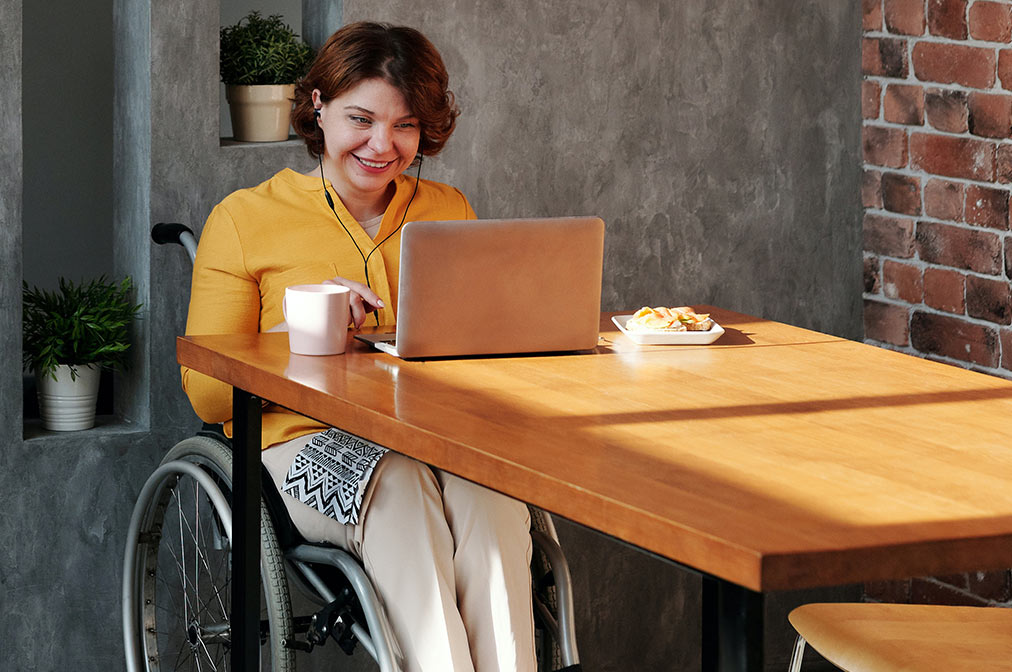 A woman who uses a wheelchair is seated at the table and smiling at her open laptop computer