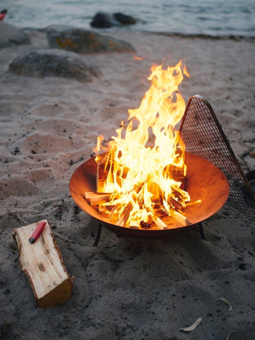 A Cricket lighter beside a blazing fireplace on a beach
