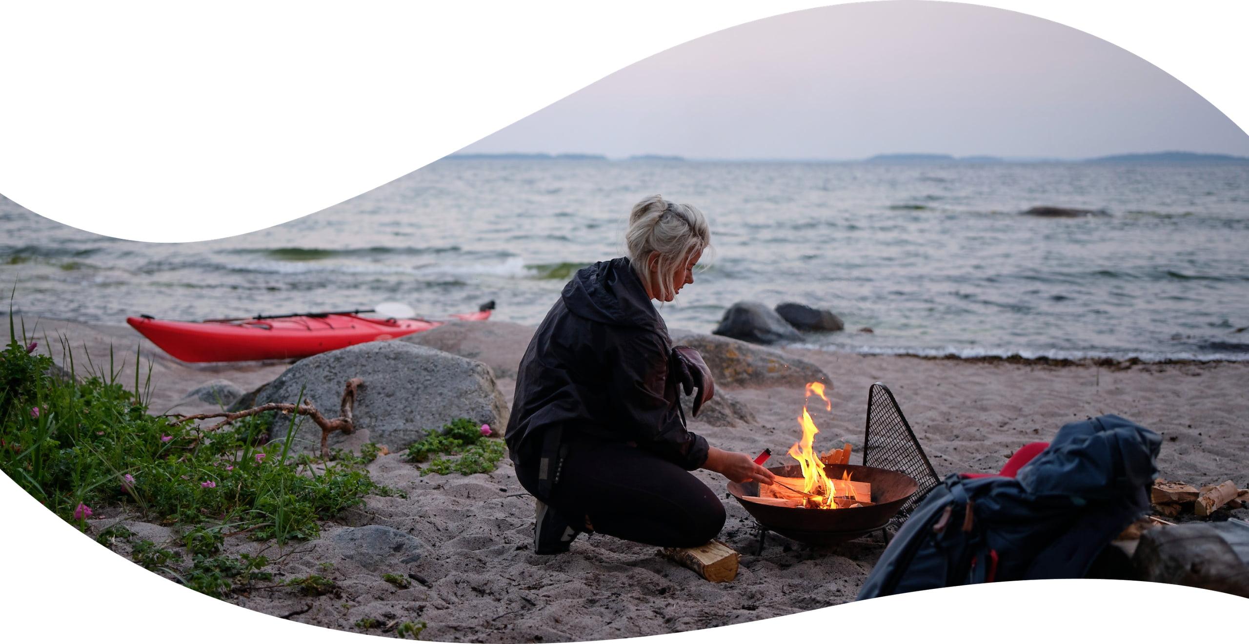Elle lighting a fire on a beach