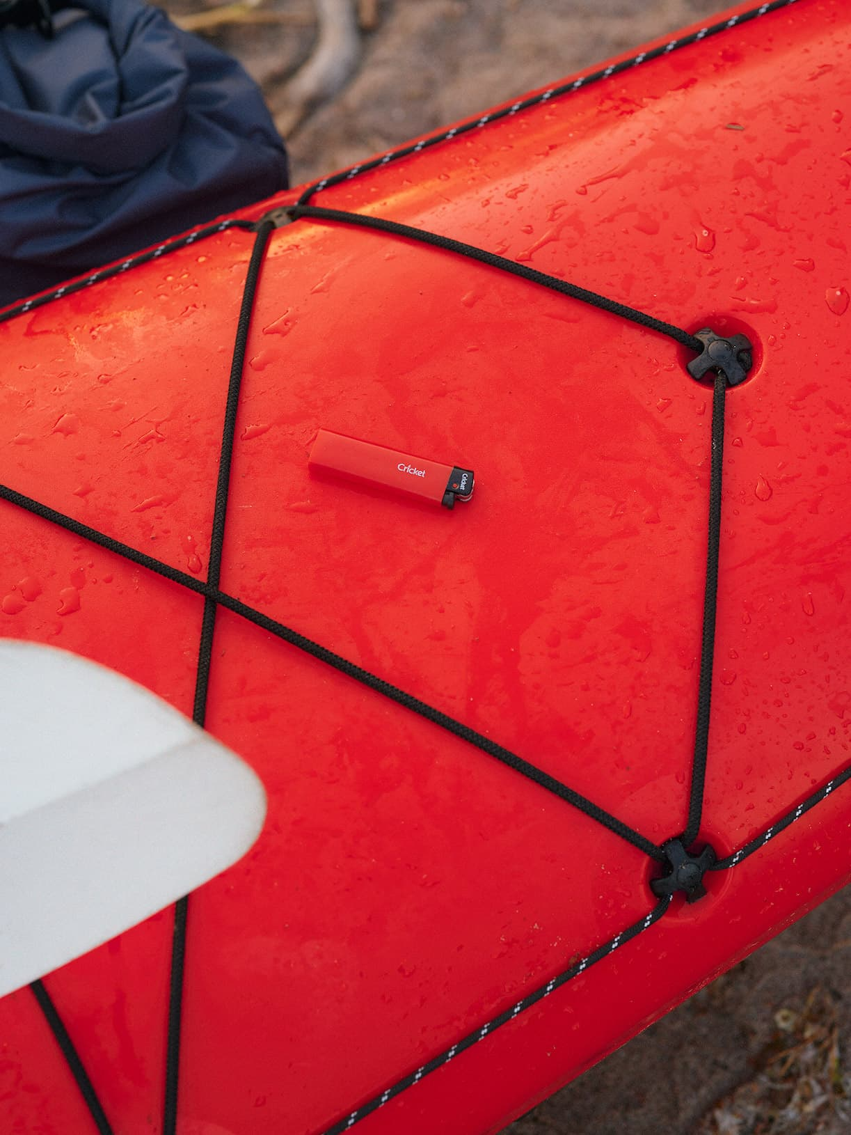 Closeup of a red kayak with a red Cricket lighter on it