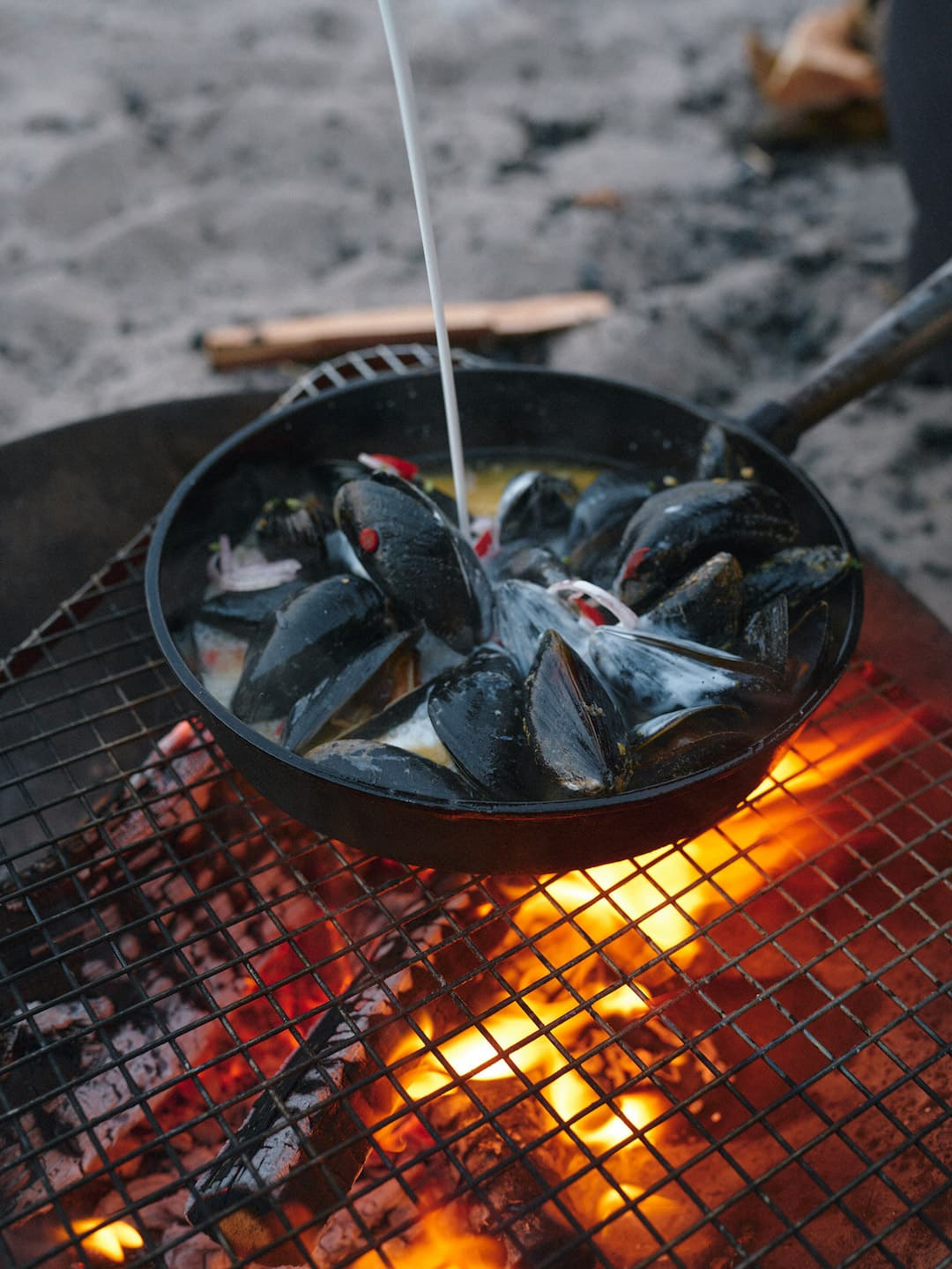Mussels being cooked in a pan on a fireplace