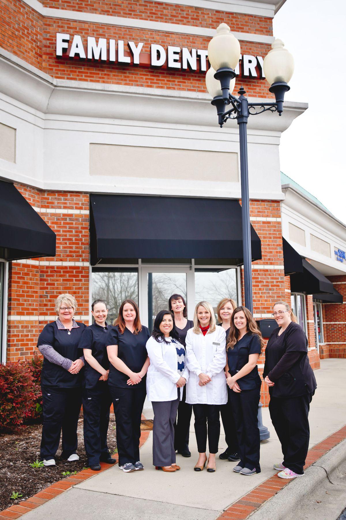 Pressley dental team smiling in front of office