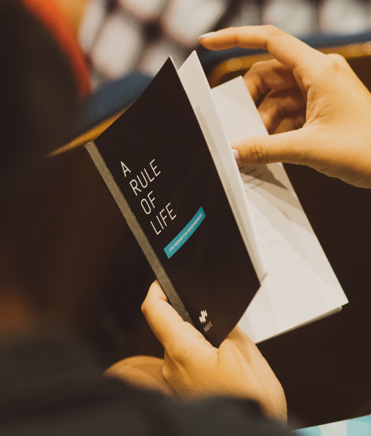 "Close-up of a person flipping through the book, ""A Rule of Life"""