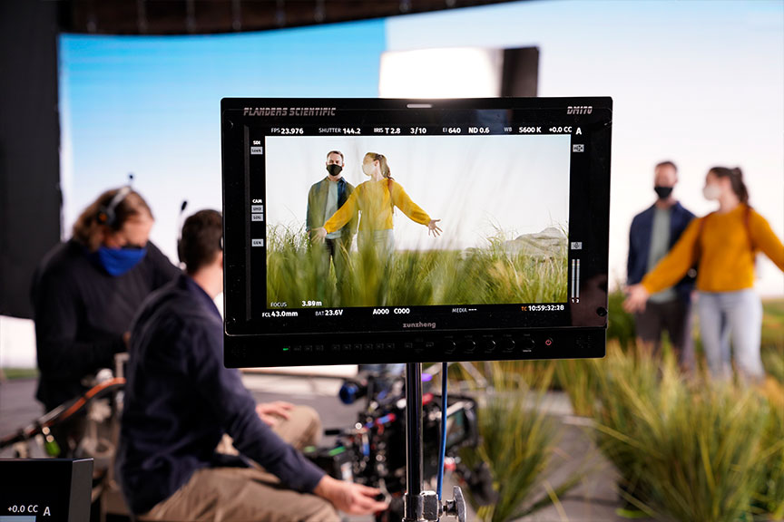 Behind the scenes image of a virtual production stage and set. The setting is a grassy meadow. A man and a woman are walking through the meadow. We see them through the camera lens.