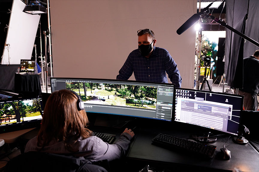Image of a man sitting behind some computers. He's working on rendering and creating the scenes that are used in virtual production.