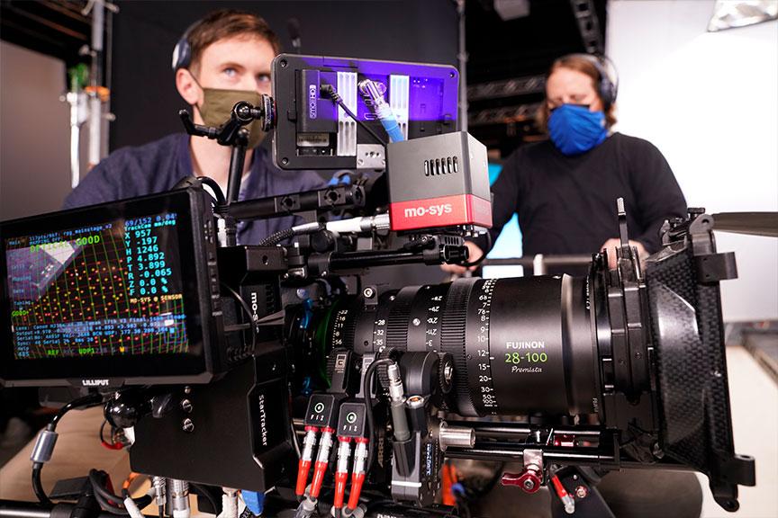 Close up image of a virtual production camera. The image displays the mo-sys tracking box and Fujinon 28-100 camera lens.