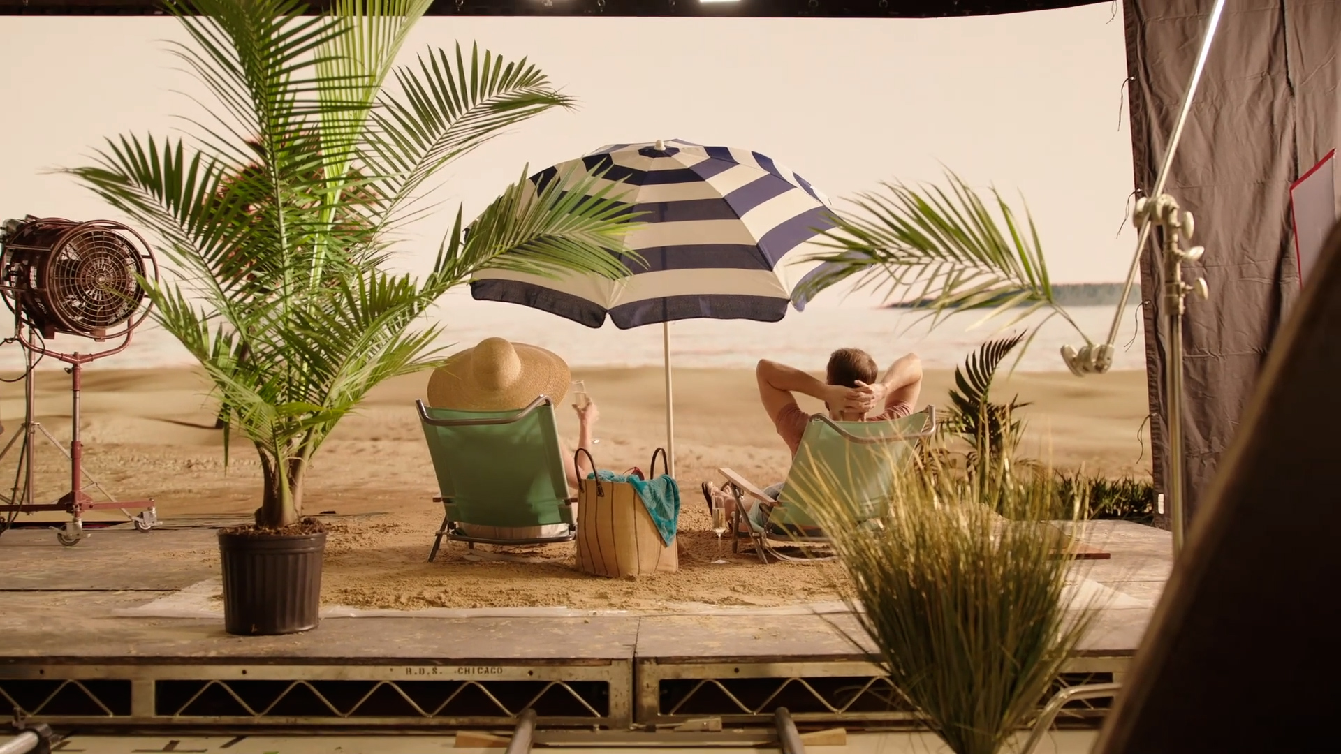 Image of a virtual production stage and set. The setting is a tropical beach. A man and a woman sit in beach chairs under an umbrella, relaxing, staring out into the ocean.