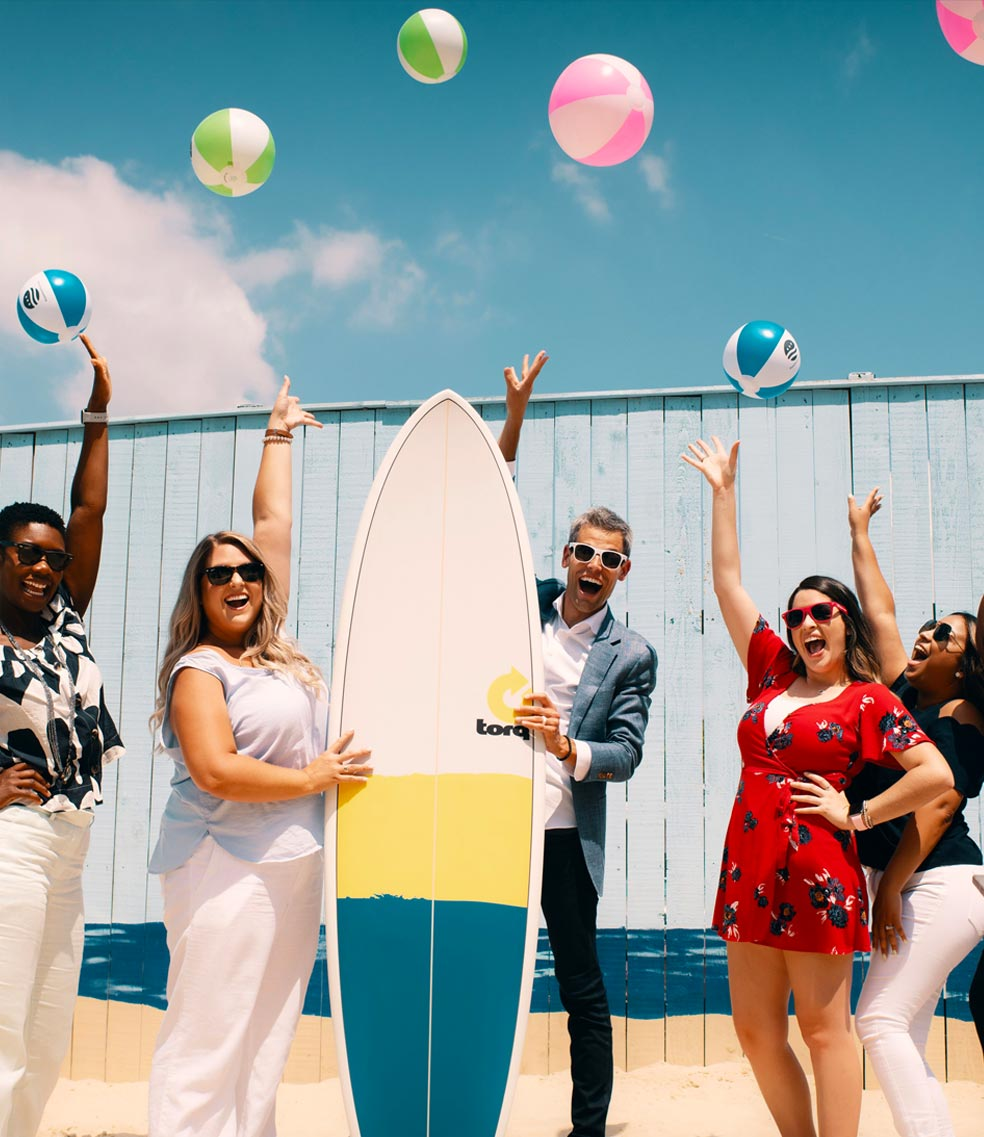 Photo of a happy pediatric dental team with a surf board and beach balls
