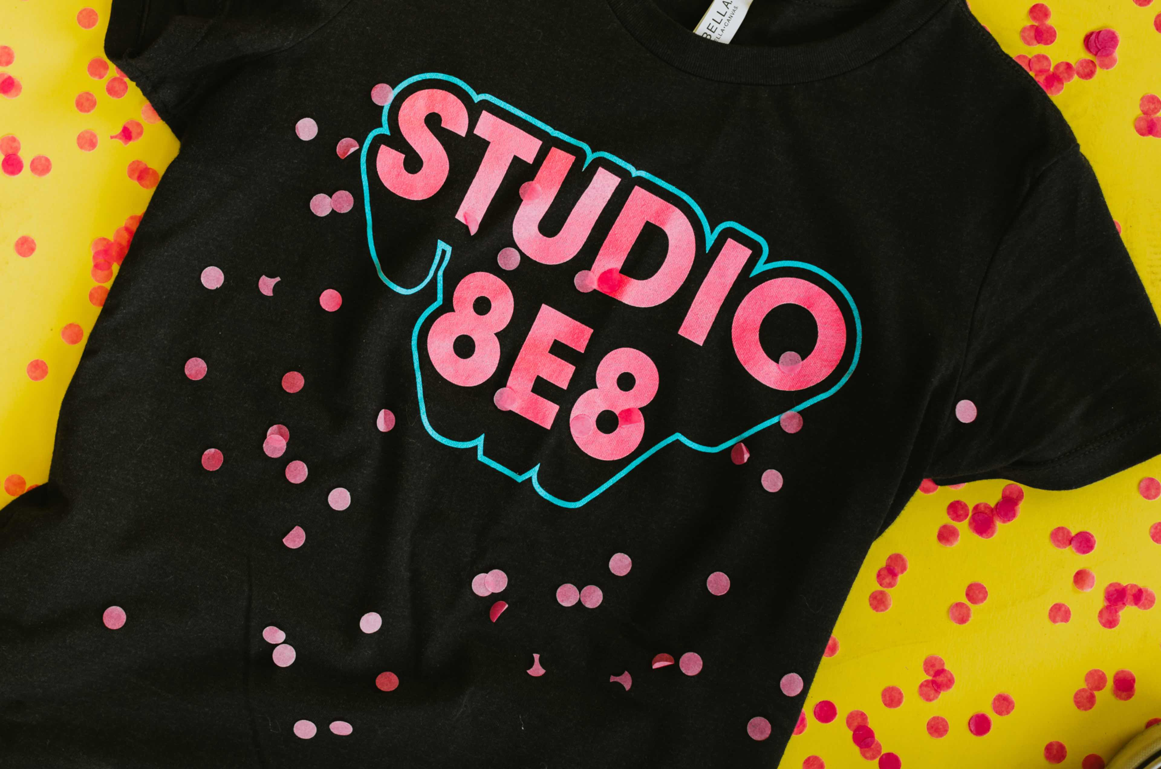 Photo of a dark gray shirt with Studio 8E8 printed on it in pink letters with a blue outline