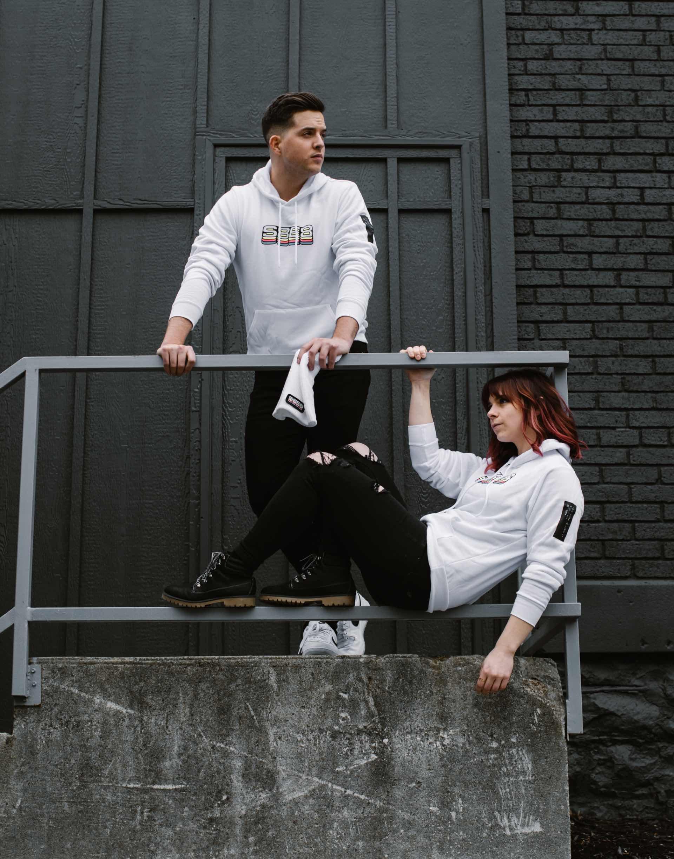 Photo of two Studio 8E8 dental marketing team members wearing their white S8E8 hoodies.