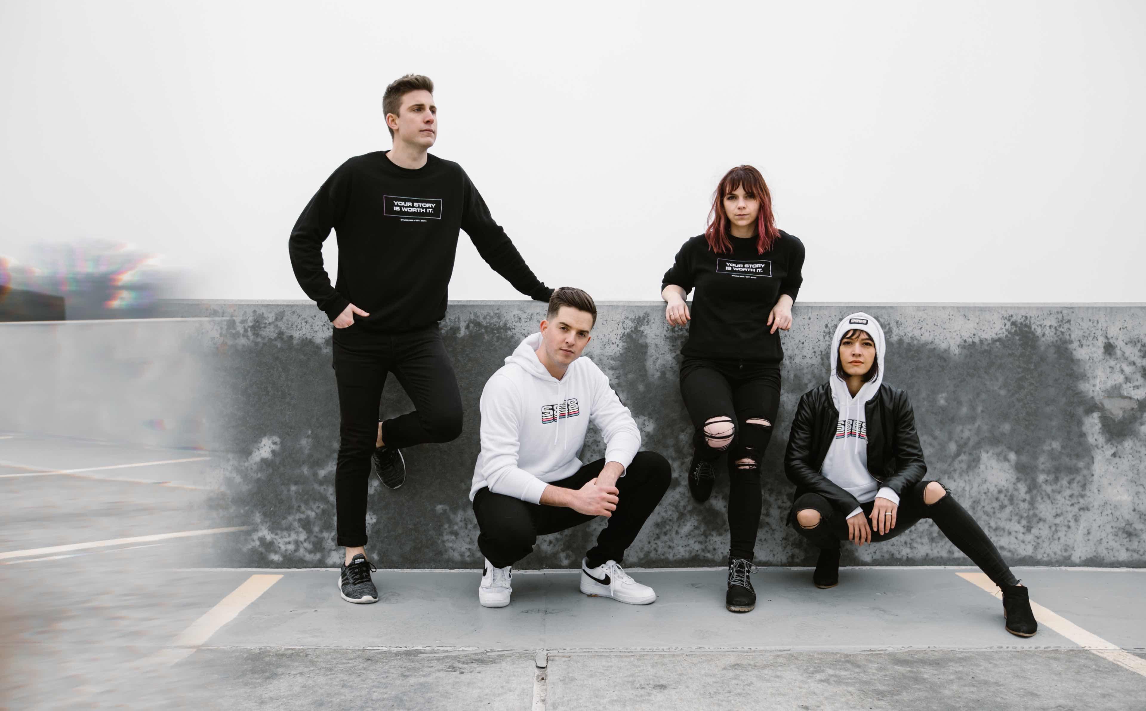 Photo of the Studio 8E8 team wearing their hoodies and sweatshirts