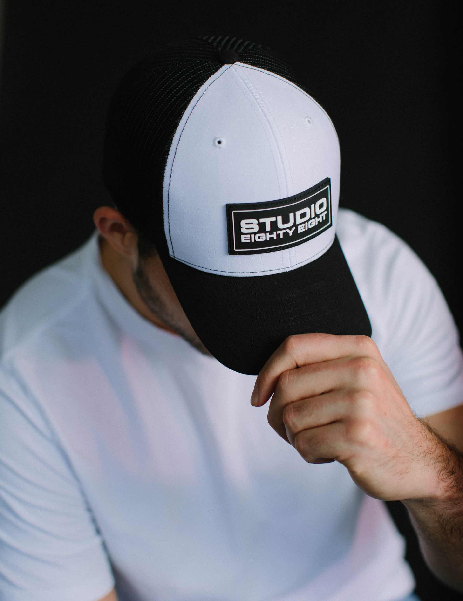 Close up photo of a man wearing a Studio EightyEight hat.