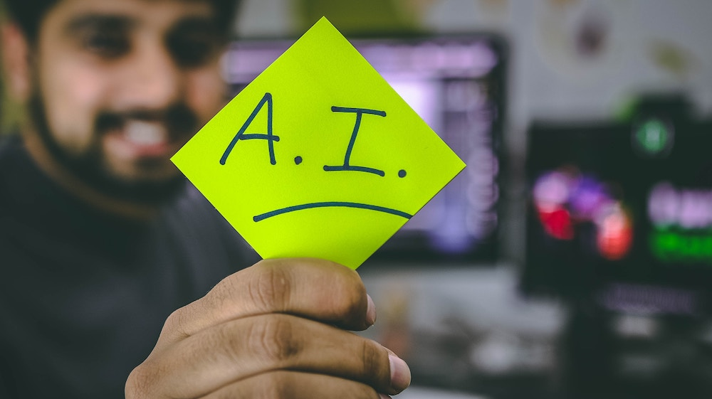 A person holding up an artificial intelligence sticky note