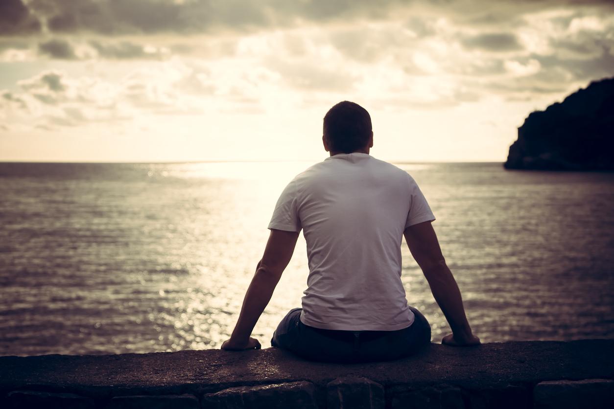 Man sits looking at the horizon