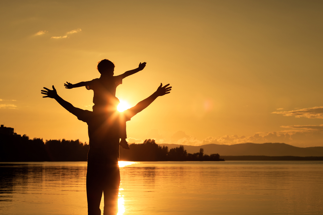 Silhouette of man holding child on shoulders during sunset