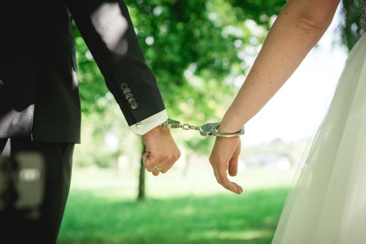 bride and groom handcuffed to each other