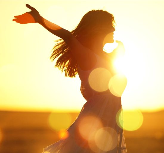 Silhouette of female with long hair and arms outstretched in sunlight