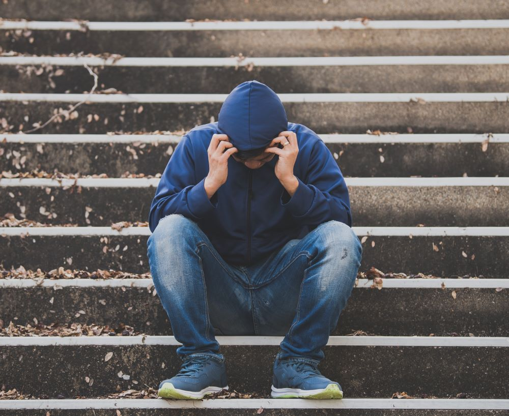 Man wearing hooded sweatshirt sitting on stairs and looking down at feet
