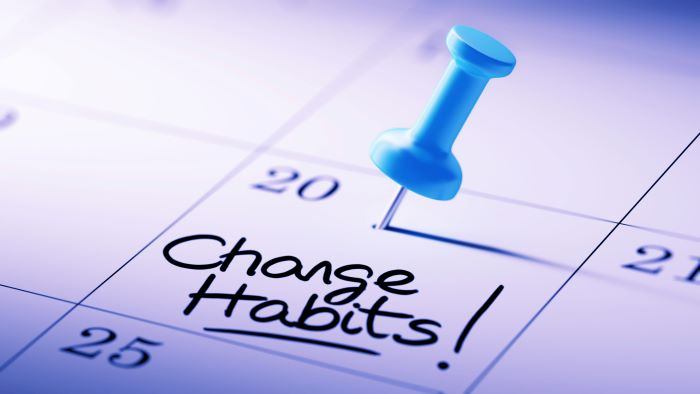 "Push pin on calendar with the words ""change habits"""