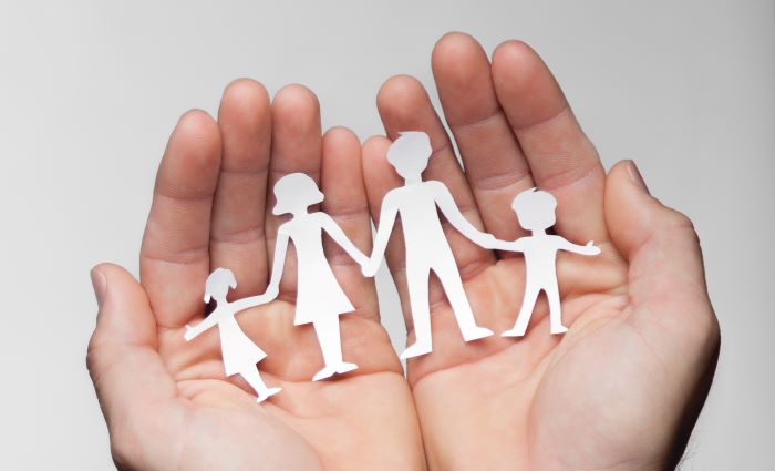 Open palms holding paper cutout of familyv