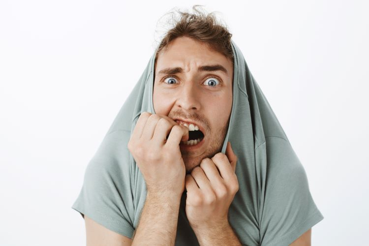 Man biting nails and trying to hide head in shirt