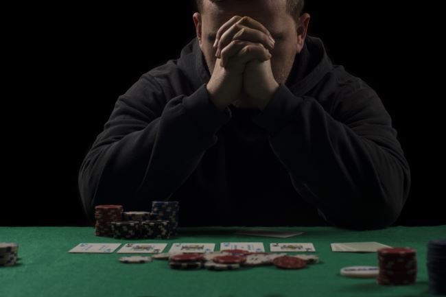 Male with head in hands sitting at a poker table