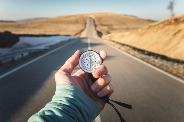 Hand holding a compass with a road in background
