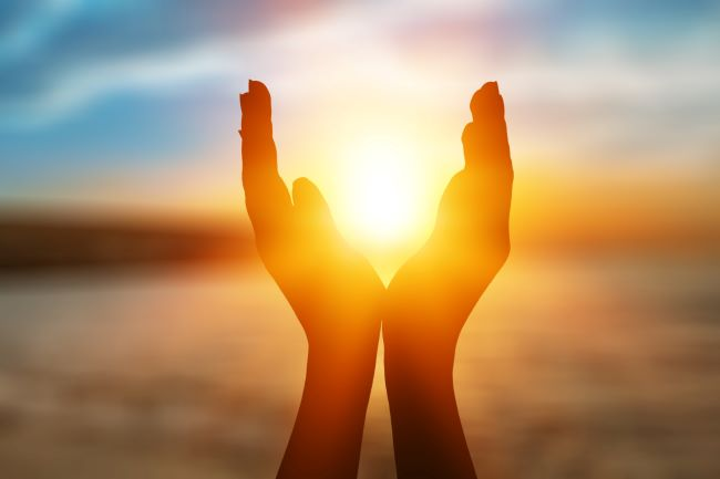 Silhouette of two hands with setting sun in background