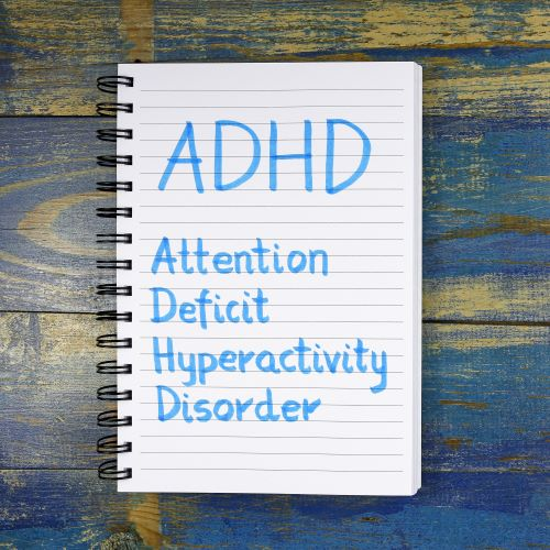 """""""ADHD- Attention Deficit Hyperactivity Disorder"""" written in notebook on wooden background"""
