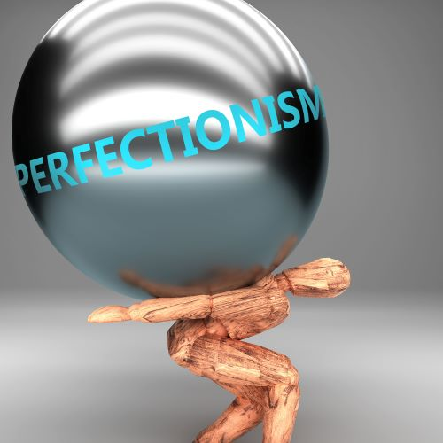 """Wooden human figure carrying large sphere that says """"perfectionism"""""""