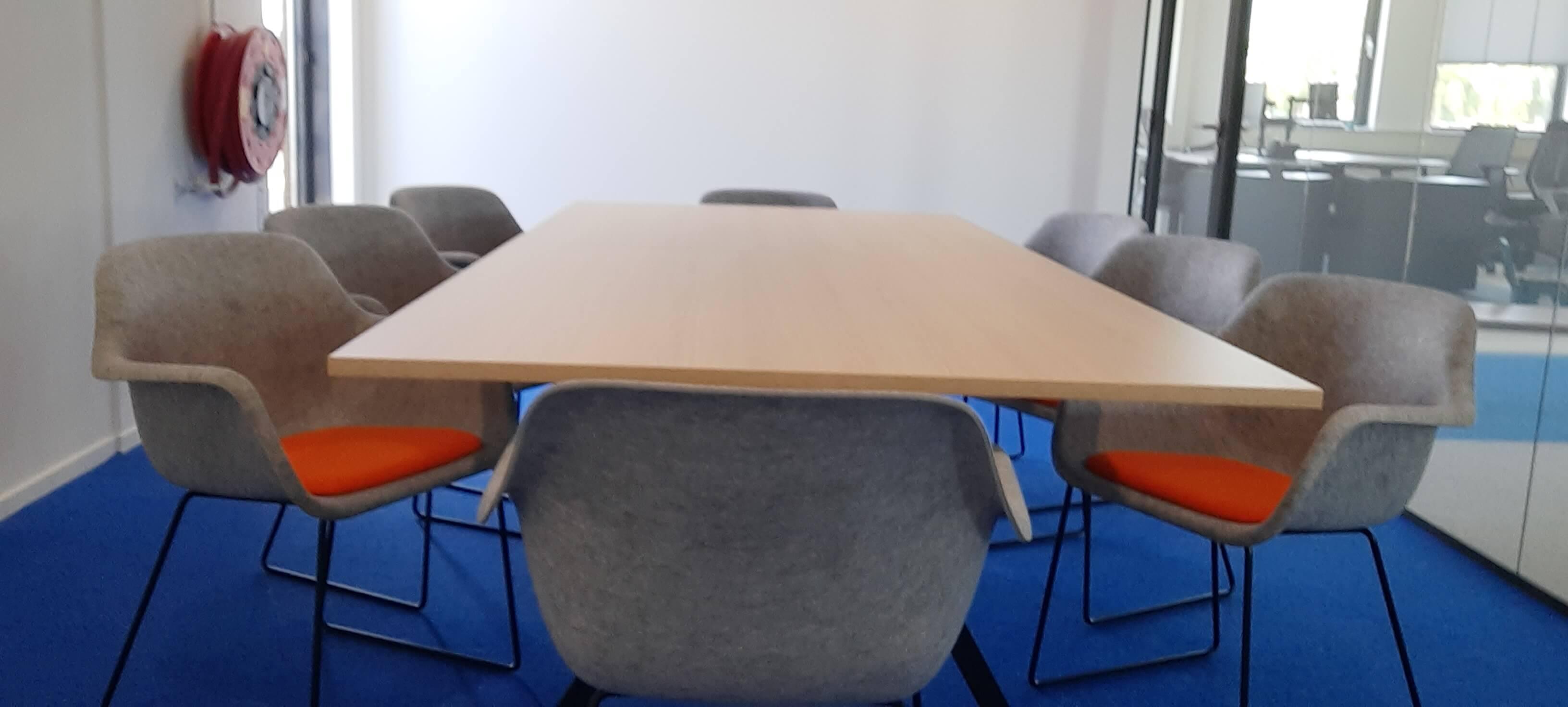 vergadertafel met stoelen in vergaderkamer